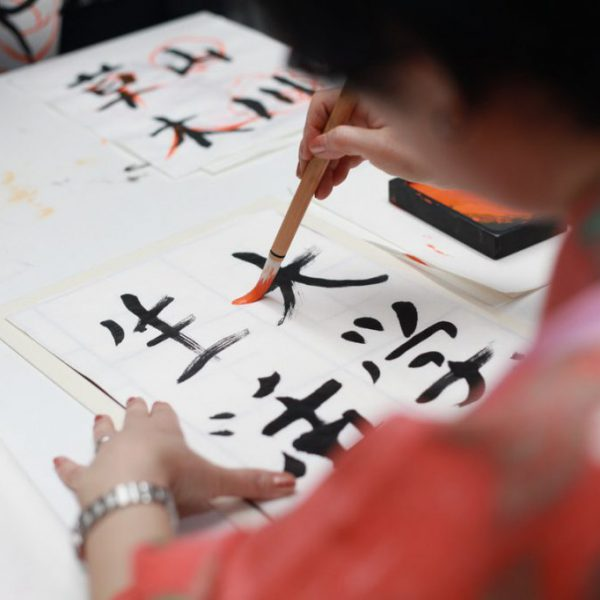 person-holding-brush-drawing-kanji-script-1498273